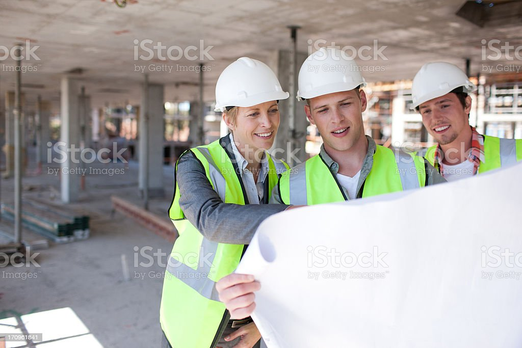 Construction workers looking at blueprints on construction site royalty-free stock photo