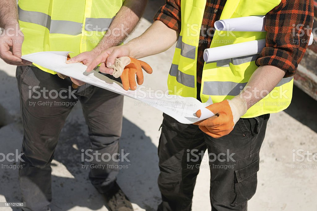 Construction workers looking at blueprints royalty-free stock photo