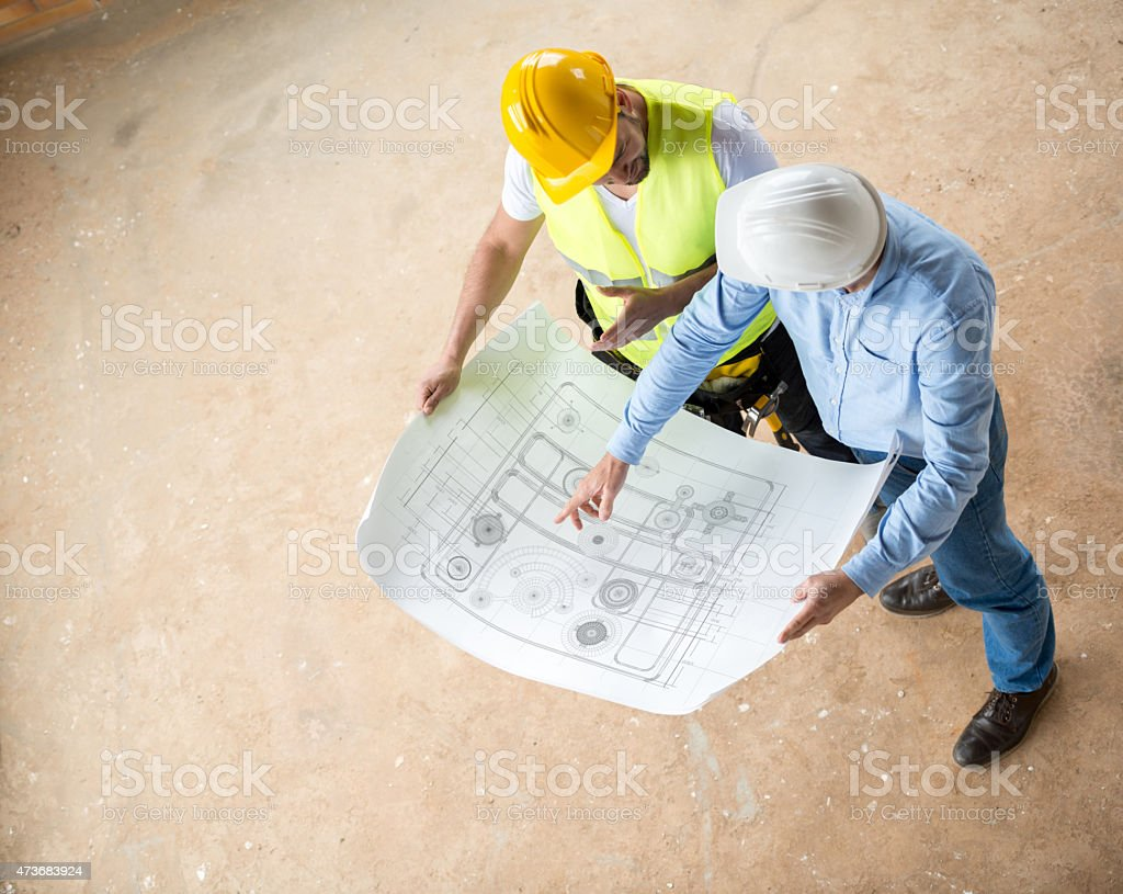 Construction workers looking at blueprints stock photo