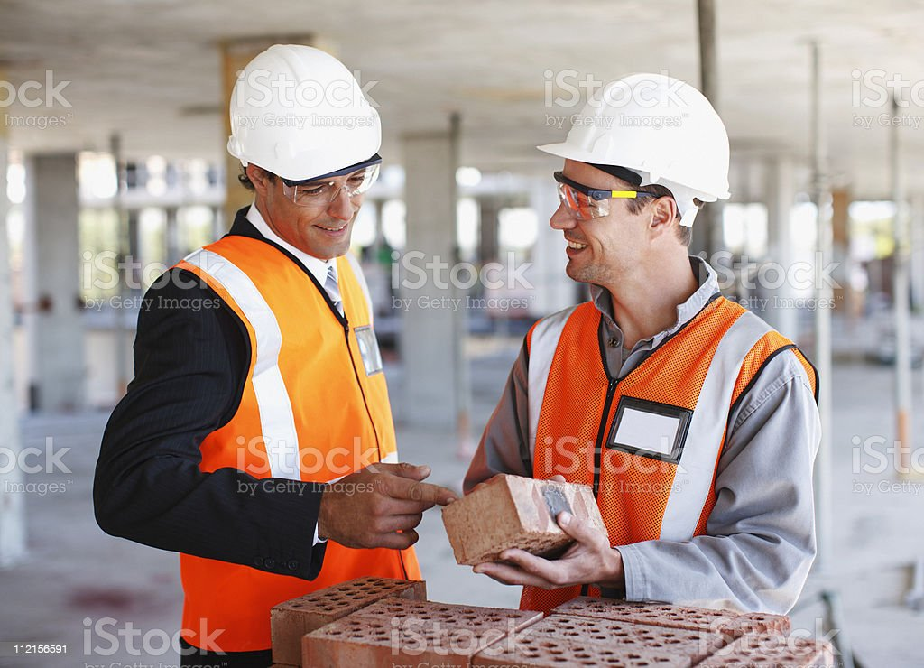 Construction workers looking at bricks on construction site royalty-free stock photo