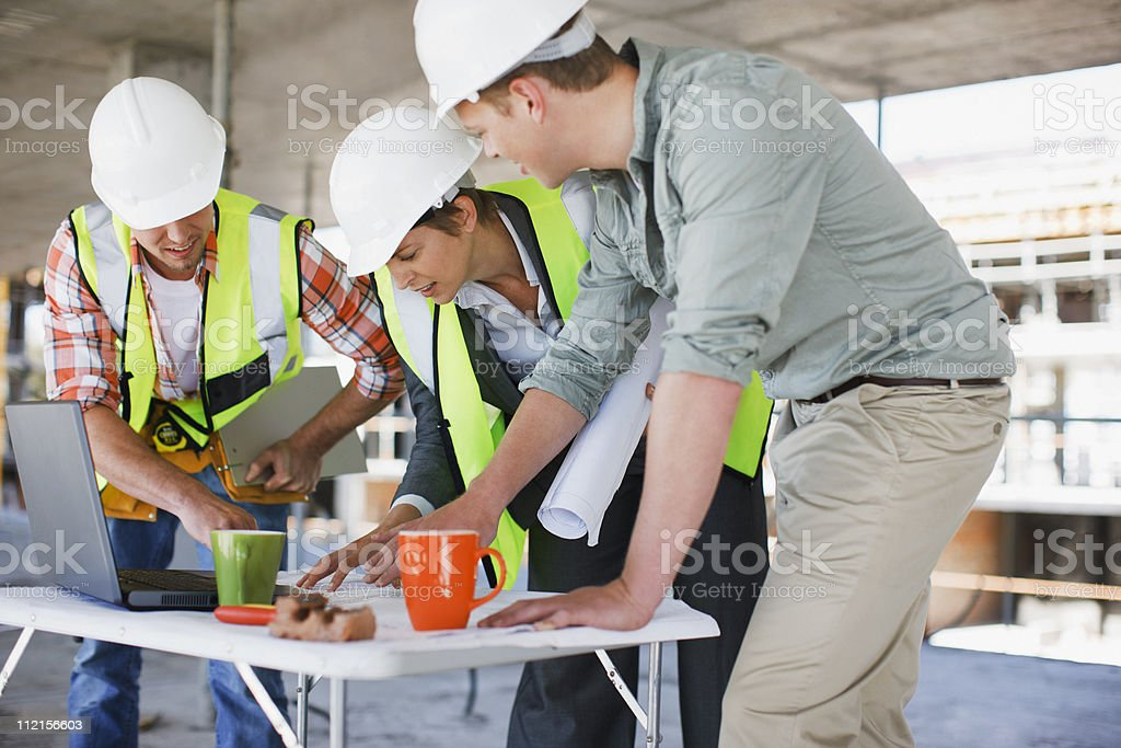 Construction workers looking at papers on construction site royalty-free stock photo