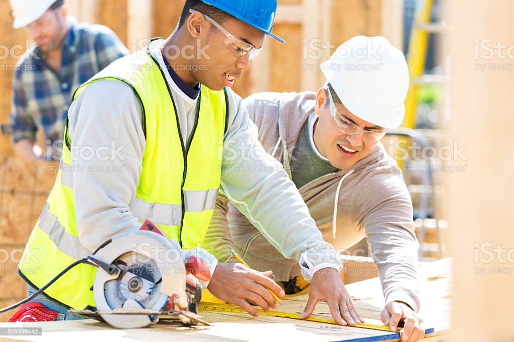 Construction workers measure board at job site stock photo