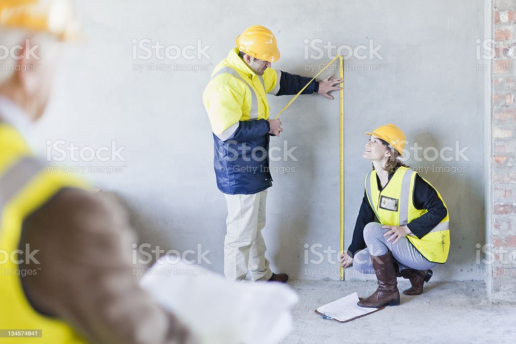 Construction workers measuring wall stock photo