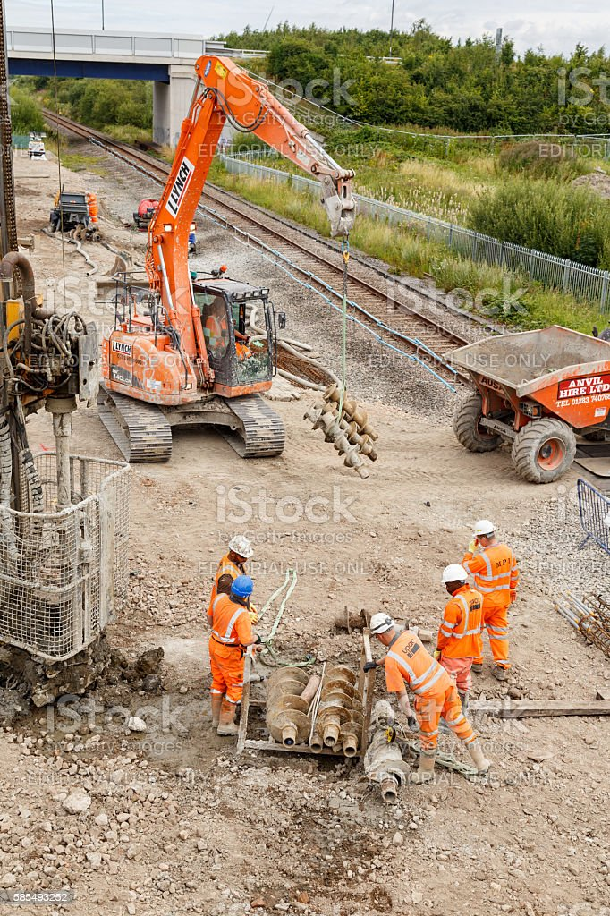 Construction workers moving helical pile drill screws stock photo
