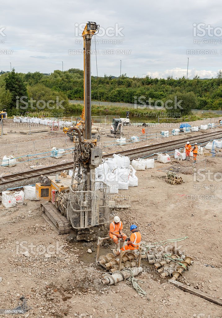 Construction workers next to a pile drilling machine, railway stock photo