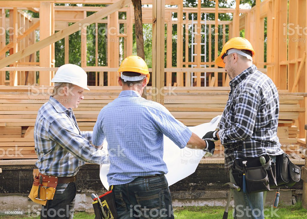 construction workers on a background of a frame house stock photo