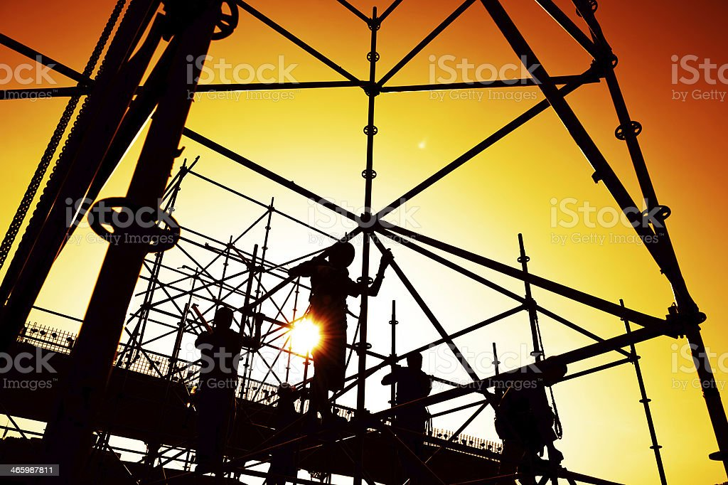 Construction workers on scaffolding at dawn stock photo