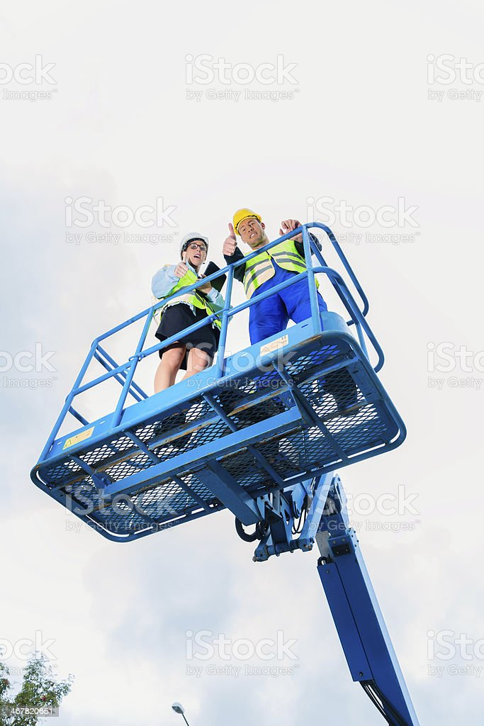 Construction workers on site in hydraulic lifting ramp stock photo