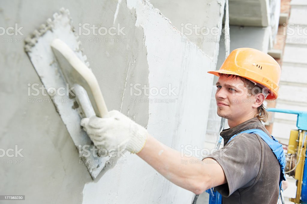 Construction workers plastering the facade of a building stock photo