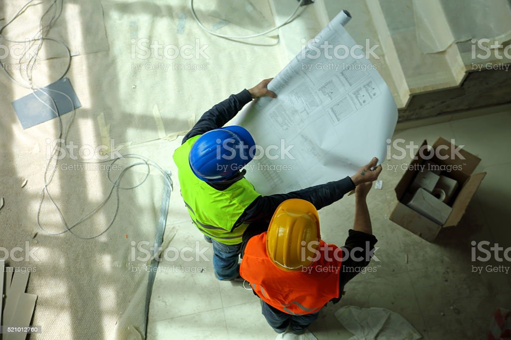 Construction workers reading blueprints stock photo