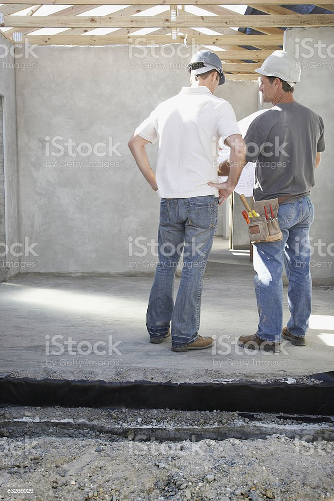 Construction workers reviewing blueprints at construction site royalty-free stock photo
