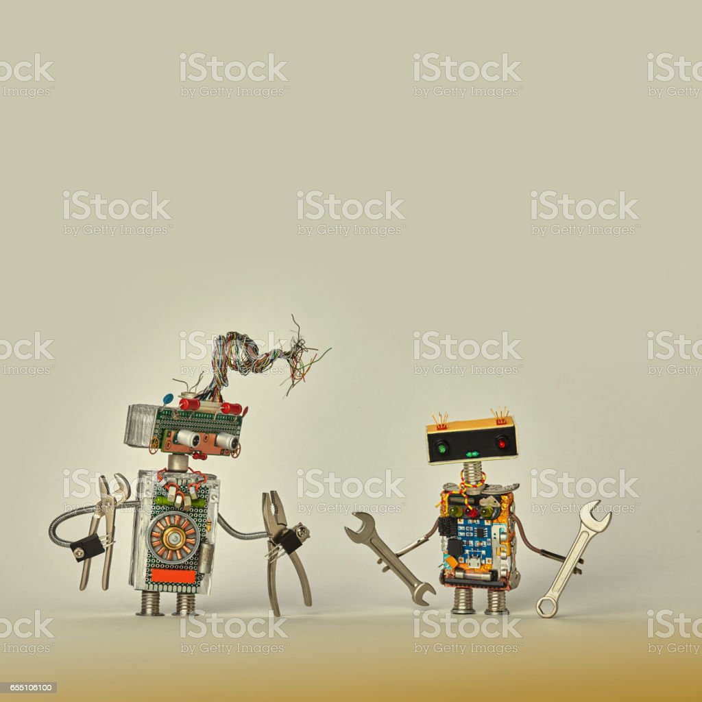 Construction workers service. Creative design toy robots with pliers hand wrench in arms. Colorful characters, wires, electronic circuit, chip capacitors resistors. Beige paper background copy space stock photo