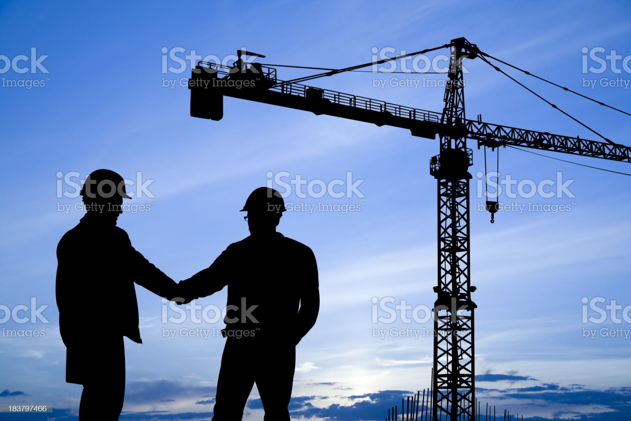 Construction workers shaking hands below crane royalty-free stock photo