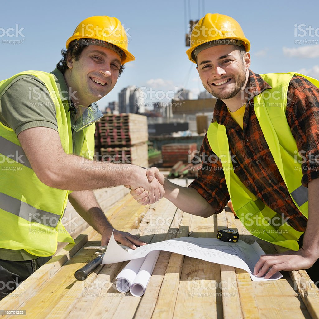 Construction workers shaking hands royalty-free stock photo