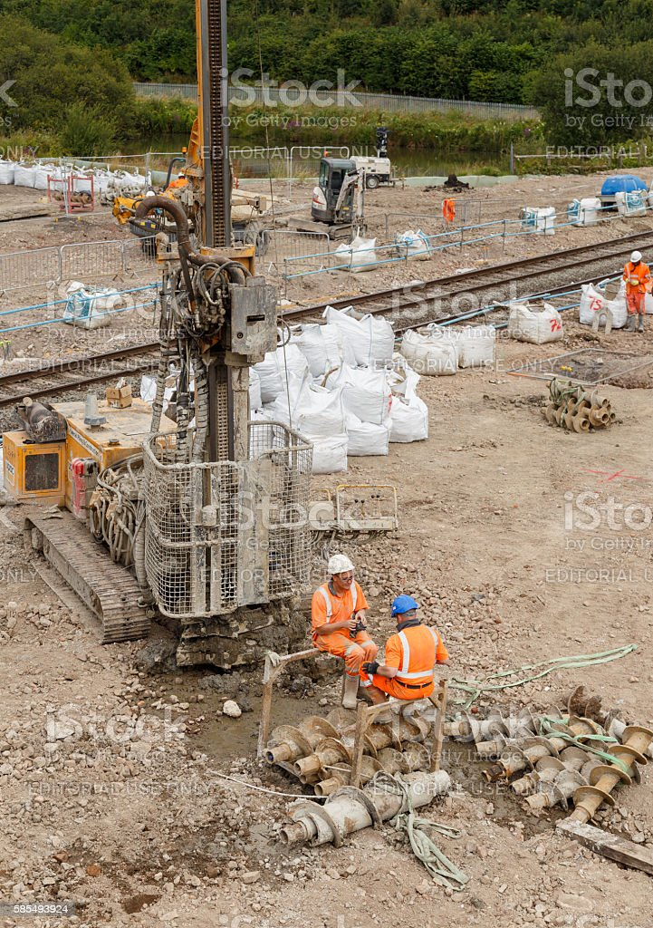 Construction workers sitting next to a pile drilling machine stock photo
