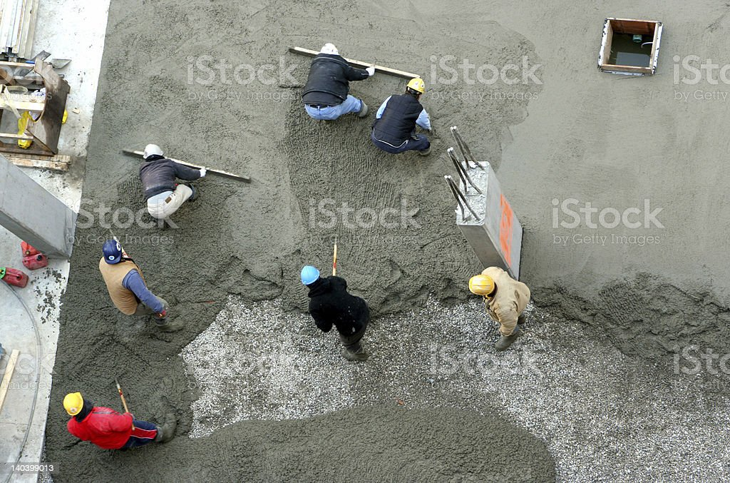 construction workers spreading concrete stock photo