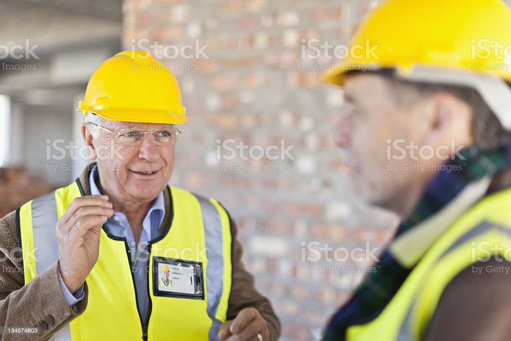 Construction workers talking on site stock photo