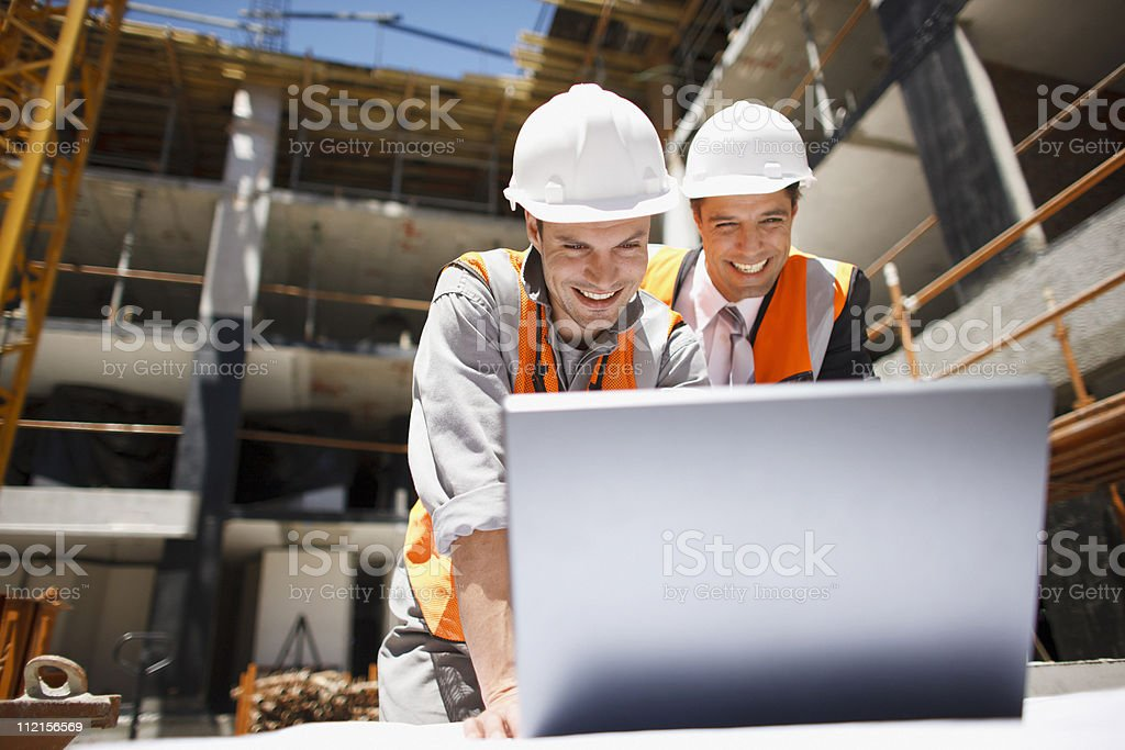 Construction workers using laptop on construction site stock photo
