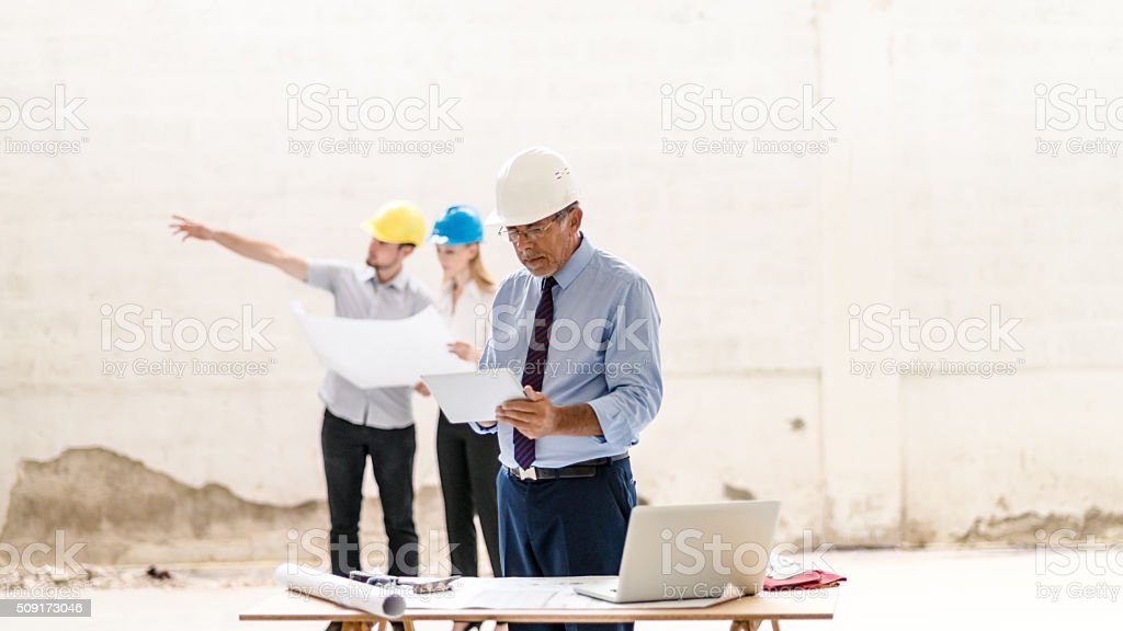 Construction workers with building plan stock photo