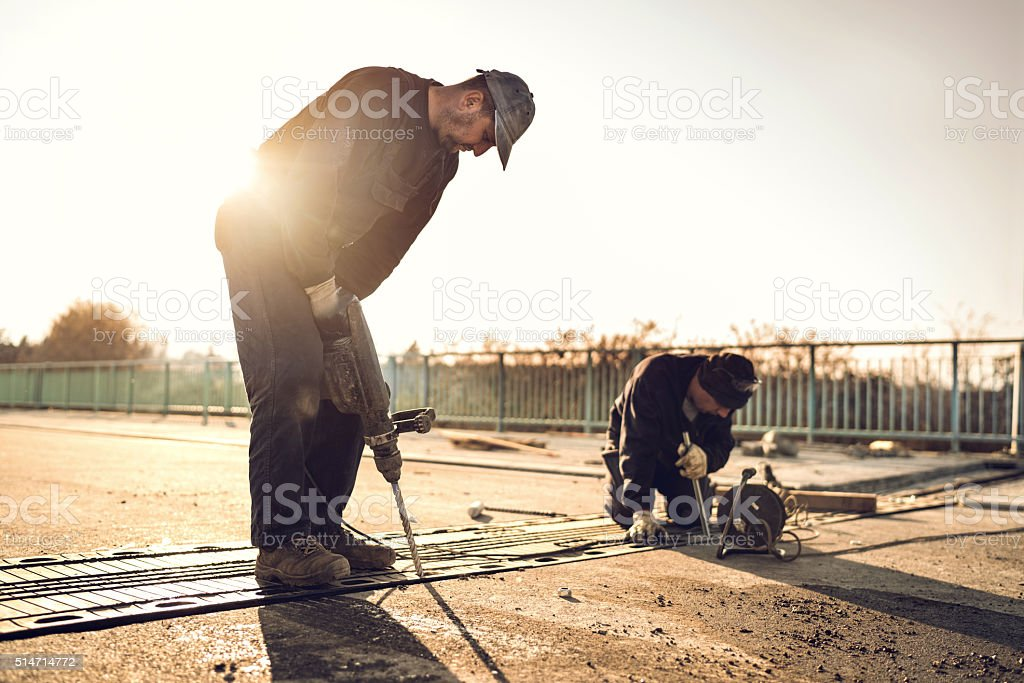 Construction workers working on road reparation at sunset. stock photo