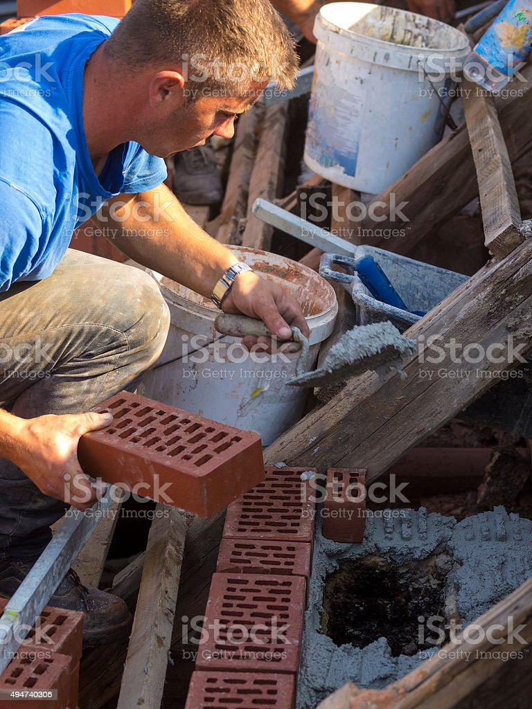 Construction works on  brick chimney, on an old roof stock photo