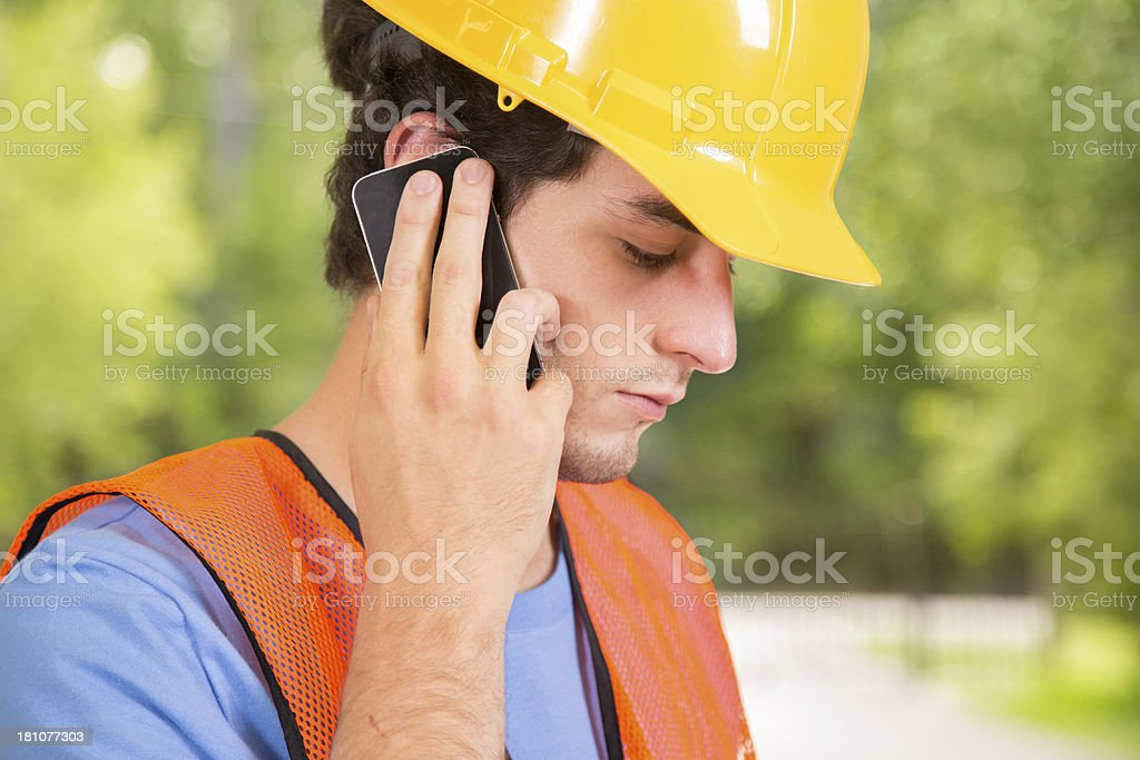 Construction:  Young man wearing hardhat talking on cell phone royalty-free stock photo