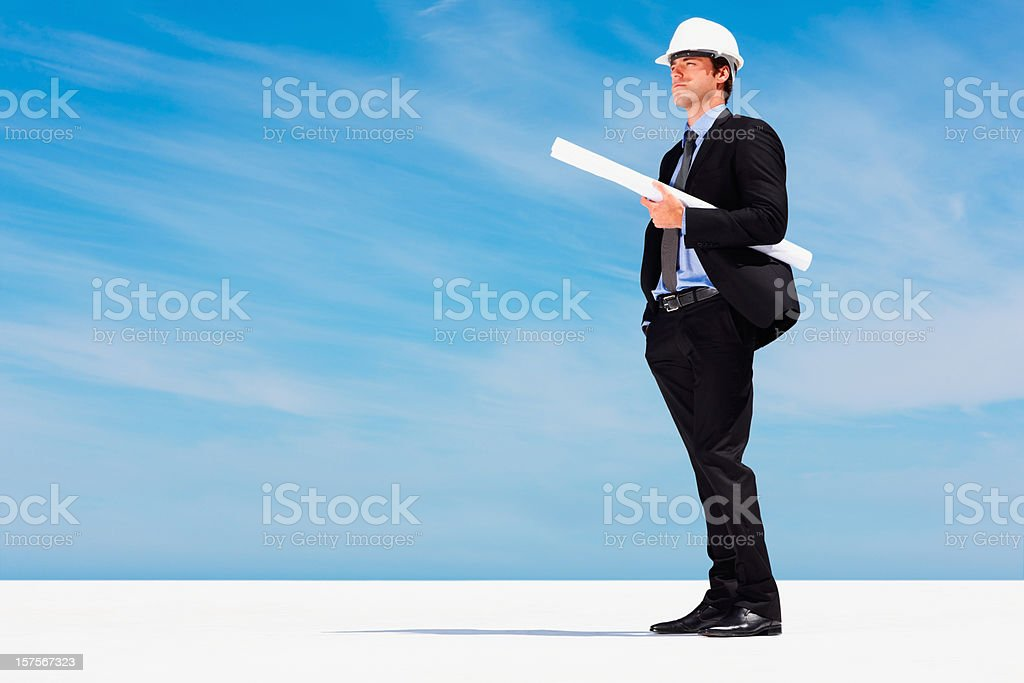 Constructor in hardhat with blueprints against blue sky royalty-free stock photo