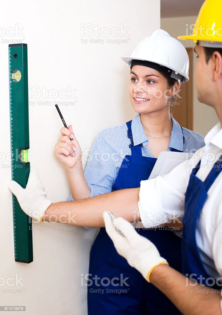 Constructor showing assistant measuring the wall stock photo