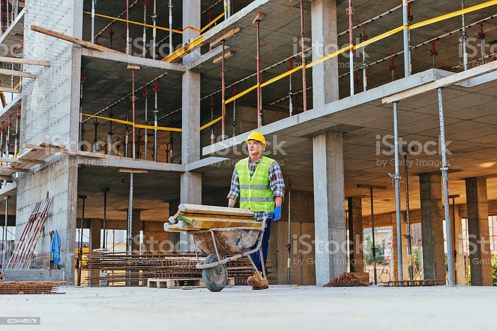 Consturction worker pushing wheelbarrow on construction site stock photo