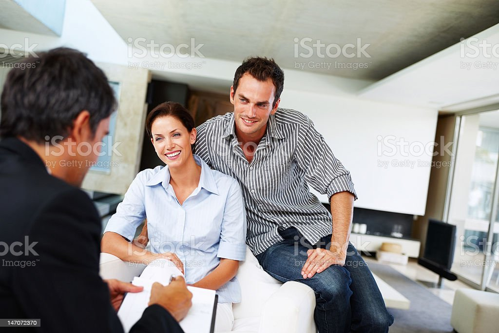 Consultant advising a young couple at home royalty-free stock photo