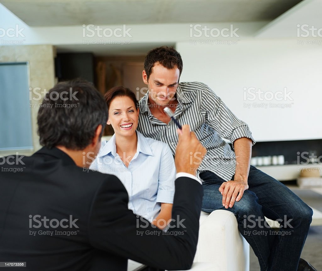 Consultant advising happy young couple at home royalty-free stock photo
