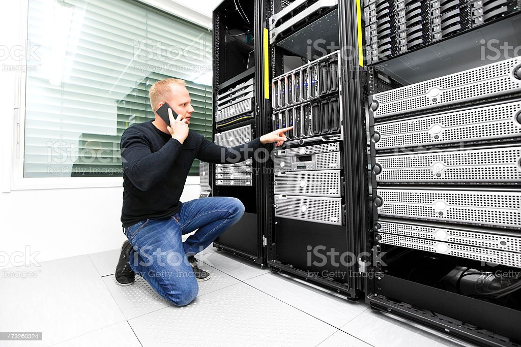 IT consultant calling support in datacenter stock photo