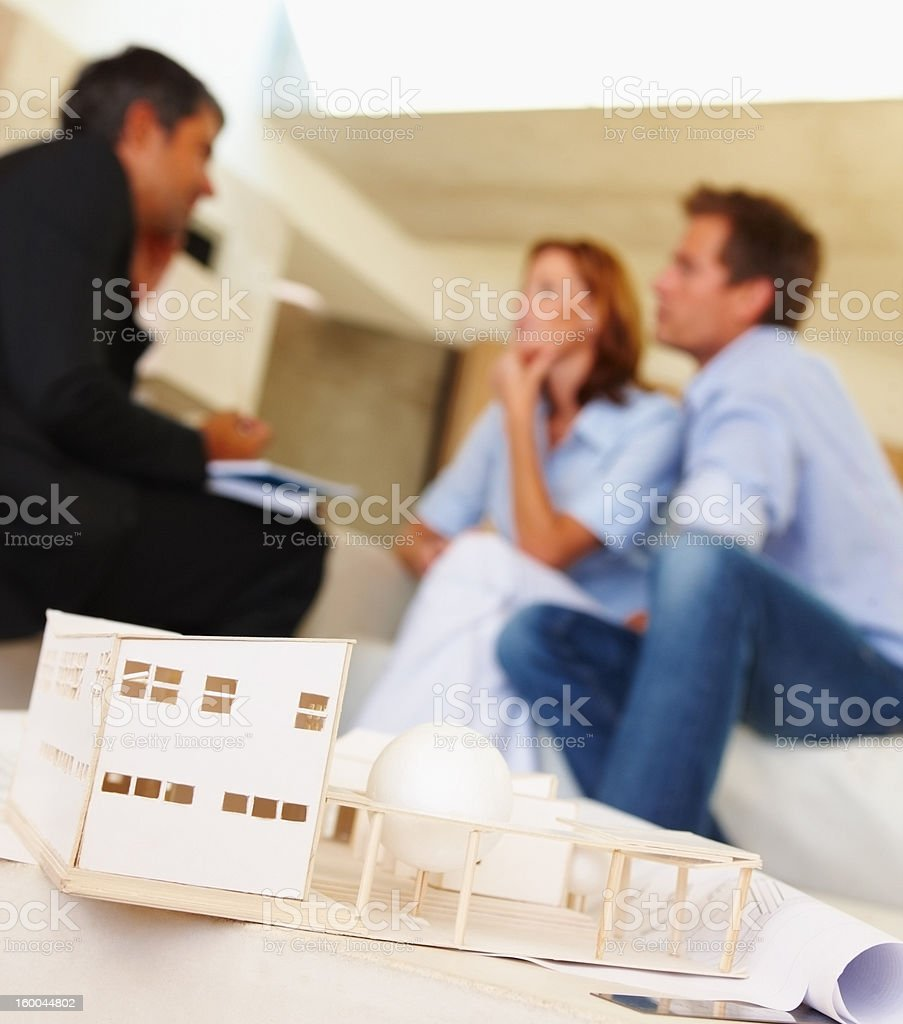 Consultant discussing a new house with couple royalty-free stock photo