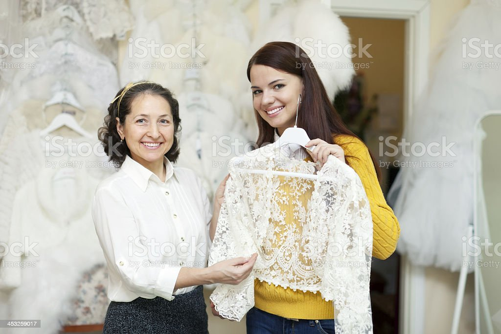 consultant helps to girl chooses  bridal clothes royalty-free stock photo