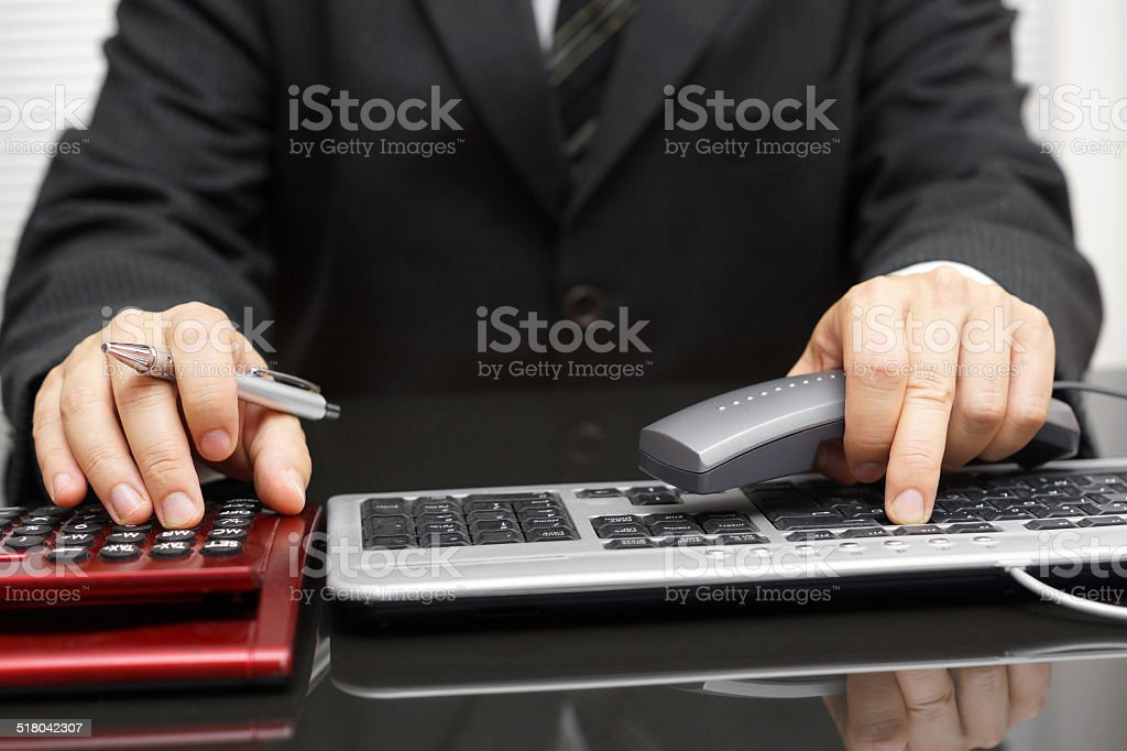 consultant is working on computer and calling client stock photo