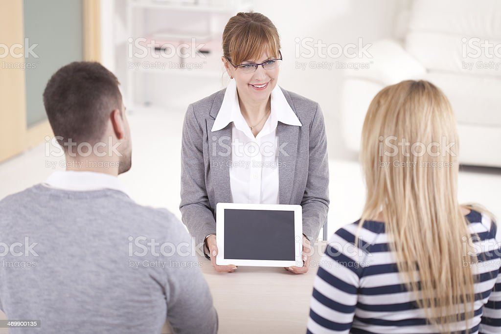 Consultant showing digital tablet to young couple stock photo