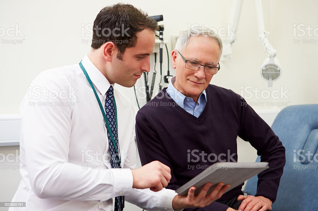 Consultant Showing Patient Test Results On Digital Tablet stock photo