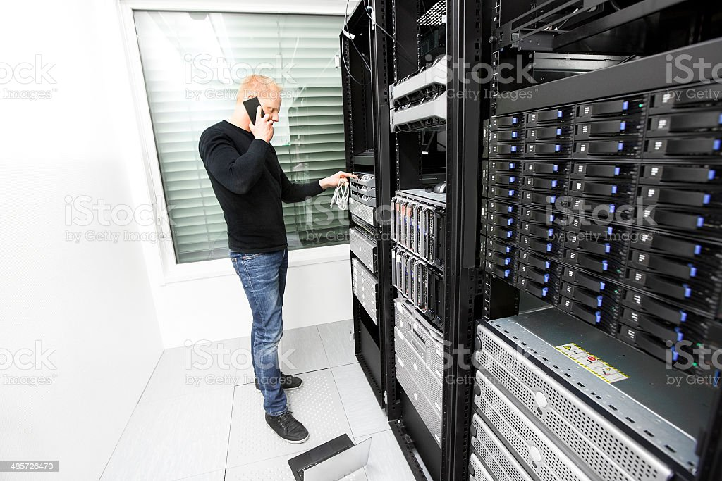 IT consultant solving problem with support in datacenter stock photo