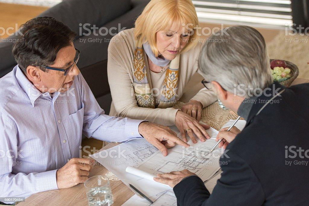 Consultant writing on blueprint stock photo