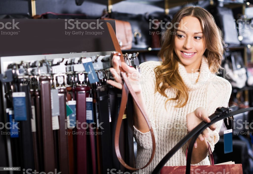 Consumer choosing leather belts stock photo