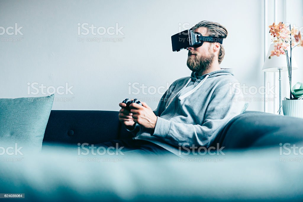 Consumer wears VR glasses and plays game at home stock photo