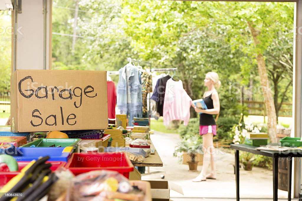 Consumerism:  Adult woman shopping at a garage sale in suburbs stock photo
