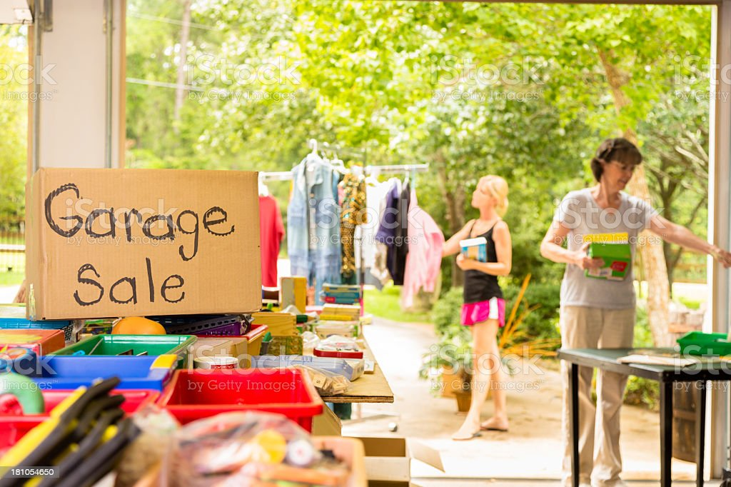 Consumerism:  Adult women buying at a yard sale in suburbs. stock photo