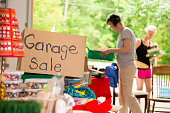 Consumerism:  Adult women shopping at a garage sale in suburbs