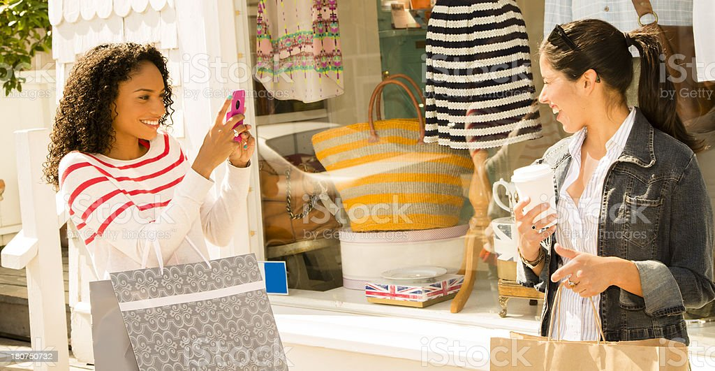 Consumerism: Friends taking cell phone pictures during shopping trip royalty-free stock photo