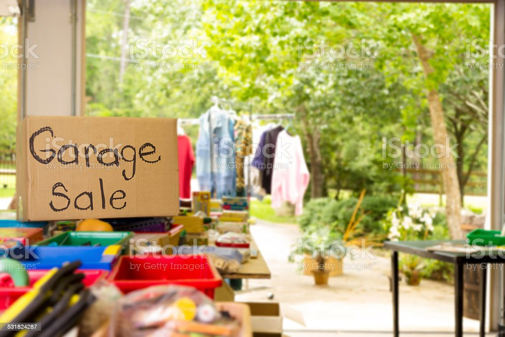 Consumerism: Garage sale posted in suburbs. Home, summer. stock photo