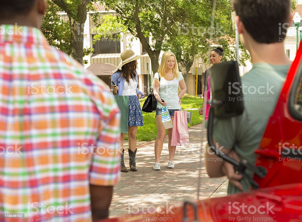Consumerism:  Males gaze at female shoppers in downtown USA. royalty-free stock photo