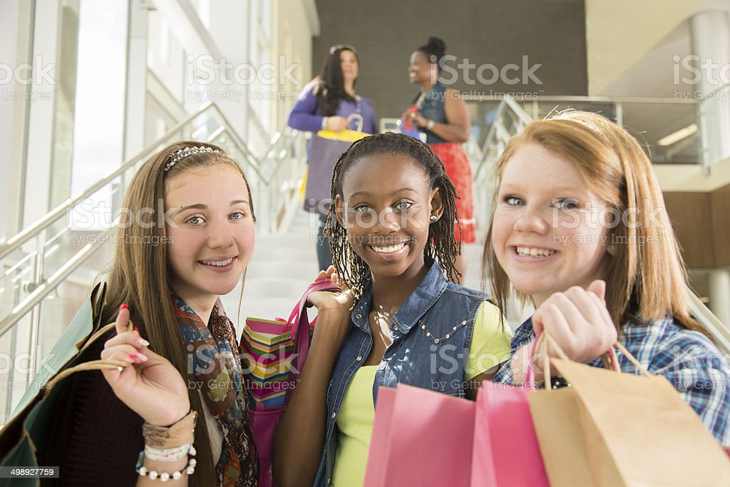 Consumerism: Mixed-race girlfriends shop in mall with shopping bags. stock photo