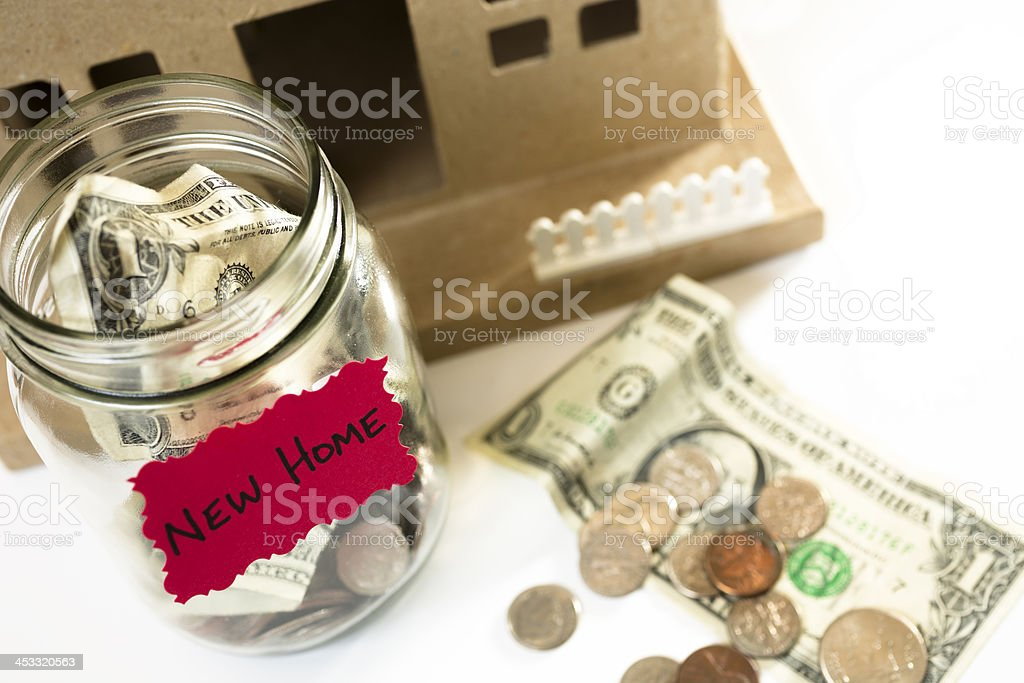 Consumerism:  Money Jar with U.S. currency.  Saving for New Home. royalty-free stock photo