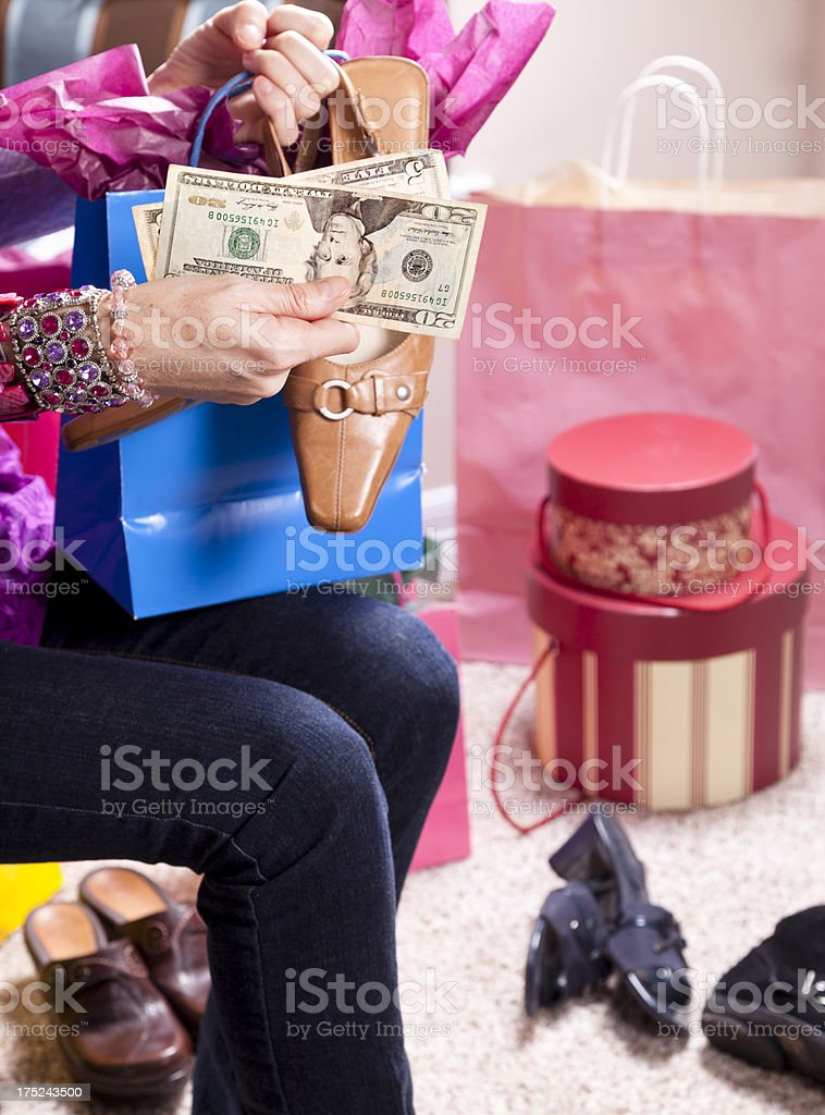 Consumerism.  Woman with money and shopping bag buying shoes royalty-free stock photo
